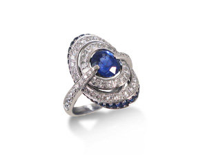 Alson Signature Collection Ring, Fashioned in 18K White Gold, Featuring a 1.69 Carat Round Blue Sapphire, Accented with Thirty-Six Round Blue Sapphries =.48cts Total Weight, Twenty Princess Cut Diamonds =.64cts Total Weight and Forty-Two Diamonds =.79cts Total Weight